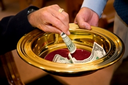 People filling the offering plate with money